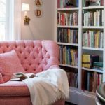 wonderful reading area with giant pink chairs also ravishing large bookshelves with marble coffee table and large white window