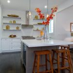 wonderufl l-shaped kitchen with wooden barstool also creative white glossy countertop with unique round scone and large potted flower in laminate flooring