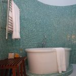 wood bench iron towel hanger white towel blue and green mosaic tiled wall white floor white oval glass tub blue and green mosaic glass tiles tube base
