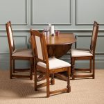 wood-polished drop leaf table three chairs with soft cotton seating and back