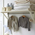 wood shelf with steel hanging rod a pile of smooth blankets hanged wool sweaters wool basket for bottle storage