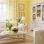 yellow painted wall yellow floral curtain light gray painted storage white sofa colorful cushions white wooden coffee table beautiful colorful flowers wooden sidetable beautiful rug