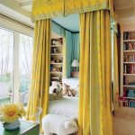 yellow patterned canopy cover white bedding set white carpet flooring green table white vase white bookshelf white ceiling floor to ceiling white framed window glass chair unique tree-like hanging lamp