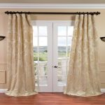 S-Shape bay window curtain with black metal hooks and stick twin ornamental wall-light fixtures in black  simple white baseboard  brushed wood finish floor