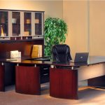 U shape desk with glossy black top desk and glass-door top cabinet system and drawer feature a black leather office chair a files arrangement