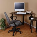 A Black Corner Desk For Monitor With Smaller Additional Panel Underneath A Messy Pile Of Books A Movable Office Chair Wood Brushed Floor An Ornamental Plant