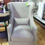 a cozy grey arm chair for reading with pearl ornaments along the edge of chair