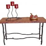 a long console table with wood top and legs like tree's branches  a chandelier with black metal stand an ornemant item