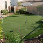 a putting green area beside a house withs  four flags feature brick fence system  beautiful landscape for outdoor