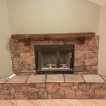 a rustic gas fireplace construction with darker cedar mantel and bricks material for wall and base of fireplace
