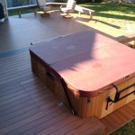 an outdoor hot tub with top cover and wood planks as its wall system a set of patio furniture wood planks flooring for outdoor area