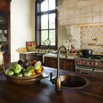 Backsplash Tiling With Spanish Tiles Material A Rustic Kitchen Set  A Kitchen Island Made From Hardwood Material Classic Sink Style With Faucet Some Decorative Items  A Big Glass Door Storage For Dishware