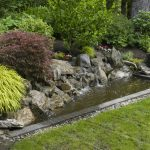 beautiful garden with natural pond full of natural stones decoration  green grass floor