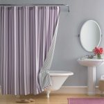 beautiful shower curtain with purple vertical strip patterns shower curtain rod white bathtub with clawfeet standing sink with faucet an oval-shape decorative mirror with  frame wood-finish floor