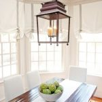 beautiful white dining seating laminated-wood planks dining table  white-theme window bay with white Roman shade bird's cage-like pendant lamp