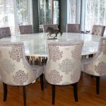 big rounded dining table with marble top expensive and elegant dining chairs wood-finishing floor for dining room large window glass with patterns
