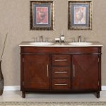 big wood vanity with cream-tone vanity surface and double round undermount vessels and faucets two decorative paintings on the wall