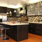 black kitchen island with glass-material bar chairs and white marble top metal-accent kitchen appliance  random-color backsplash three cute pendant lights top and under black wood kitchen cabinetry