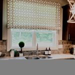 brown Roman window cover with beautiful patterns for window garden in kitchen  a kitchen sink and faucet natural stone tiles for backsplash area