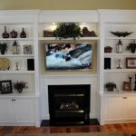 built-in shelving unit and cabinets beside the fireplace unit TV set on fireplace box top some beautiful ornaments round side-table with classic table laminated-wood flooring