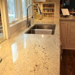 Cashmere White Granite Countertop With Double Deep Stainless Steel Sinks And A Single Stainless Steel Faucet Hardwood Floor Idea With Clear Lines A Sugar Container Made From Glass Under Kitchen Cabinet