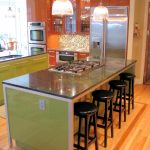 chic-colors kitchen island  with glass top and black round bar chairs wood-brush floors  twin large pendant light fixtures some modern and electric kitchen appliances