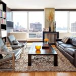 comely living room concept with wonderful brown leather sofa and large glass window overlooking the city view feat large bookshelves and elegant brown fur rug in laminate flooring