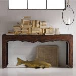 console table in rustic style with piles of papers a unique hanging chandelier a fish ornament