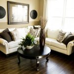 corner modular white sofa with various patterned pillows  a round table in black wood finishing black wood planks flooring some wall ornaments