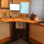 corner standing computer desk with three flat screens a small audio system a unique metal table lamp a white wireless keyboard and  white tea pot
