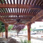 dark wood finish lattice patio cover with ceiling fan in black