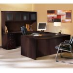 dark wood finishing U shape office desk with transparent door cabinets and drawer a flat computer  dark leather office chair classic white table lamp with golden-accent stand an abstract painting no frame