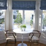 darker blue up-down sliding Roman window shades for window bay casual couple arm chairs with white round table green small decorative plants and pots laminate wood flooring