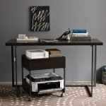 darkwood-finish printer desk with wheels a printer machine paper supplies  on top panel an office desk in darkwood finish decorative painting on the wall pile of books on office desk