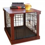 dog crate with wood laminating top for table  a yellow cup and a pile of books