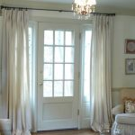elegant long white curtains for French door a corner arm chair with standing lamp behind it some wall decorative items a classic pendant lighting