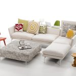 elegant white modular sofa with colorful decorative pillows and small plastic chair in red