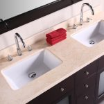 extra large bathroom vanity with double square white  deep undermount sinks  stainless steel faucets light brown marble vanity surface black-framed decorative mirror a pile of red towel supplies