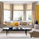 floor to cealing drapes bay windows units sweet yellow wall color  twin grey velvet-coat sidetable with black decorative vases cozy and luxurious living room furniture