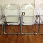 four sets of folded-Lucite chairs with transparent seating and back panels brushed-hardwood floor