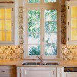 fresh spanish tiles in backsplash area a glass window in the center of kitchen room a deep stainless steel sink with faucet glass-door top kitchen cabinets