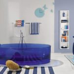 glass blue tub with stainless steel water sprayer white-blue strips carpet white-blue strip patterns  towel white towel light blue wall ornaments transparent glass table with blue vase ornament  vertical shelf for bathing properties