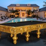 golden-accent private pool table with black top large outdoor pool some pool furniture black ceramic tiles flooring in pool area