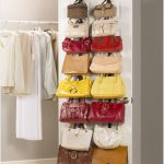 hanbag collections on the back door of changing room several hanging clothes a pair of sport shoes in white color