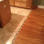 hardwood to tile floor transition with small mosaic tiles as the divider a kitchen set and kitchen island