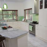 kitchen island with seating and cahsmere white granite top a modern kitchen set in white with modern kitchen appliances green-cover pendant light fixtures large white ceramic tiles for kitchen floor