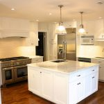 Kitchen Remodel In White Simple Style White Kitchen Island With Storage And Sink Plus Faucet Gold Tone Appliance Of Kitchen Simple White Under And Top Kitchen Cabinetry Wood Flooring Idea