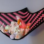 knitted-wool hanging storage for stuffed animals in black and pink colors
