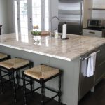 large white marble countertop with bar backless chairs sink and faucet a roll tissue stand cut-board and a fruits basket darkwood finish flooring some kitchen appliances