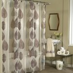 leaves-patterns shower curtain with curtain rod a wood-framed decorative mirror a cart for sink and faucet a minimalist console table with metal legs